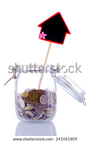 Jar filled with coin and black board house shaped, isolated white - stock photo