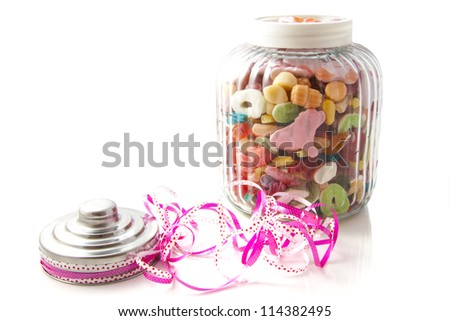 Jar filled with colorful candy isolated over white