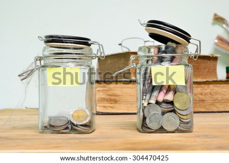 Jar for savings full of coins on wood. - stock photo