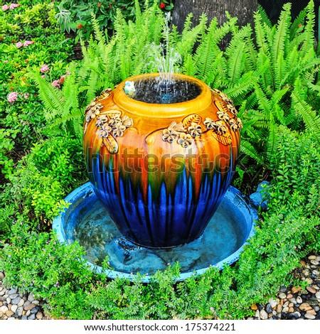 Jar fountain in the garden. - stock photo