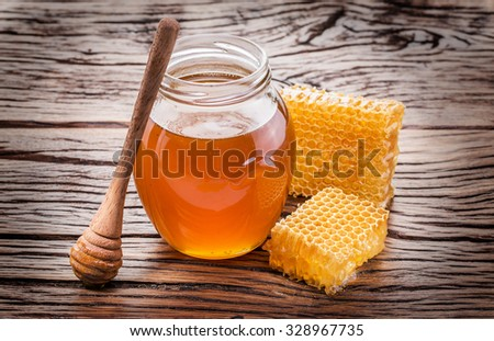Jar full of fresh honey and honeycombs. High-quality picture. - stock photo