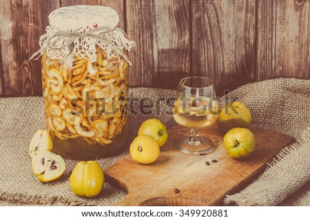 Jar of alcoholic tincture and glass of drink with quince fruits on a jute background. - stock photo