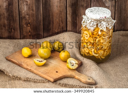 Jar of beverage with quince fruits on a wooden table covered with sackcloth. - stock photo