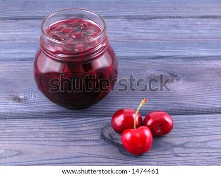 jar of cherry jam and some cherries on board
