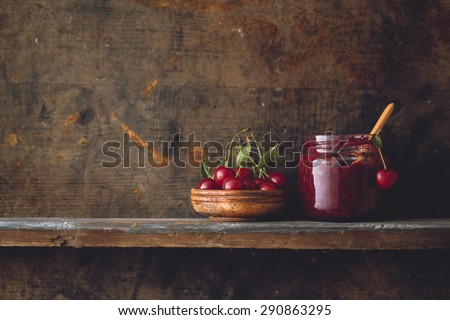 Jar of cherry jam and sour cherries on wooden shelf - stock photo