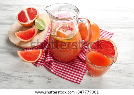 Jar of citrus juice and fresh fruits on light wooden background - stock photo