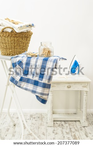 Jar of clothes pegs and basket of fresh laundry with iron in the background - stock photo