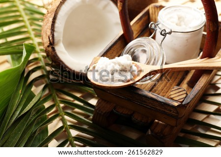 Jar of coconut oil with coconut and leaves on table close up - stock photo