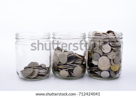 Jar of coins and money in white background