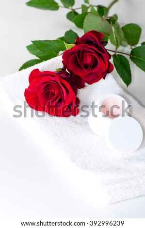 jar of cream with red roses and a white towel