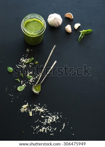 Jar of fresh home made pesto and ingredients for it. Fresh basil leaves, grated parmesan cheese and garlic over black backdrop. Top view, copy space - stock photo