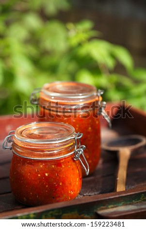 Jar of home made classic spicy Tomato, Chillie, garlic and Peper sauce salsa - stock photo