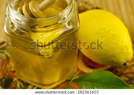 Jar of honey a wooden spoon and lemon on a table