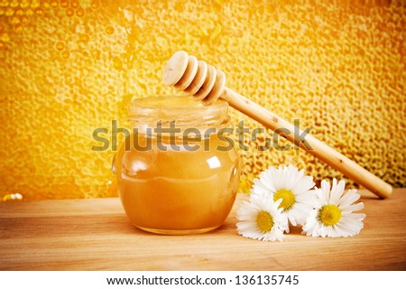 Jar of honey and flovers. On the background of honeycombs - stock photo