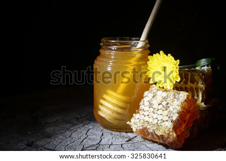 jar of honey and honeycombs on a wooden background - stock photo