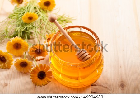 Jar of honey and wooden wand on a wooden background - stock photo