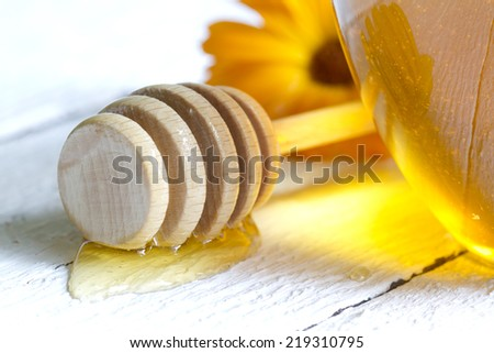 Jar of honey closeup on white planks - stock photo