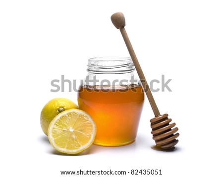 Jar of honey with a wooden drizzler and lemons. Isolated on white background. - stock photo