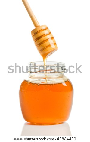 Jar of honey with drizzle stick on white background - stock photo