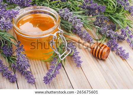 jar of liquid honey with lavender. artificial flowers - stock photo