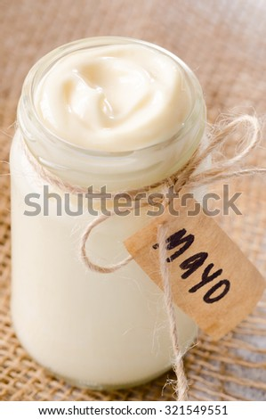 Jar of mayo with label on hessian, a salad dressing or sandwich condiment - stock photo