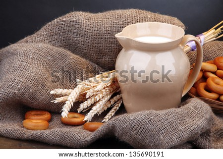 jar of milk, tasty bagels and spikelets on wooden table, on grey background - stock photo