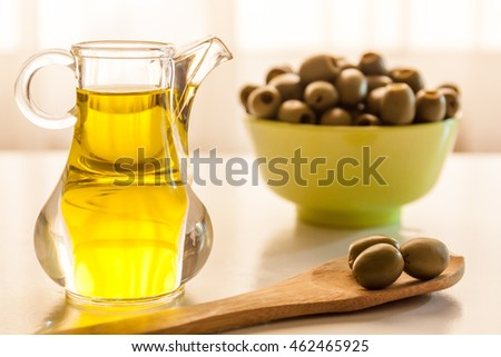 Jar of Olive oil, wooden spatulas and a bowl of seedless olives on a table
