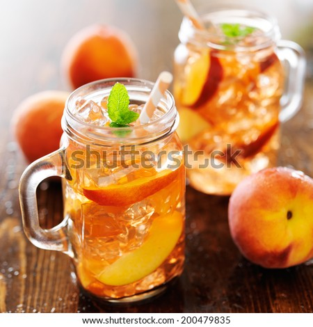 jar of peach tea with striped straw - stock photo