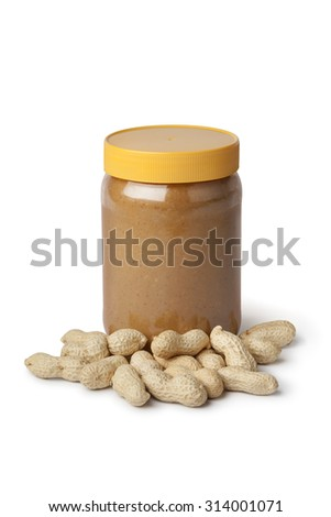 Jar of peanut butter and peanuts on white background - stock photo