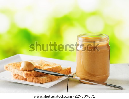 Jar of peanut butter and toasts on nature background. - stock photo
