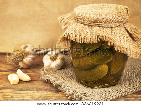 jar of pickles on burlap napkin - stock photo