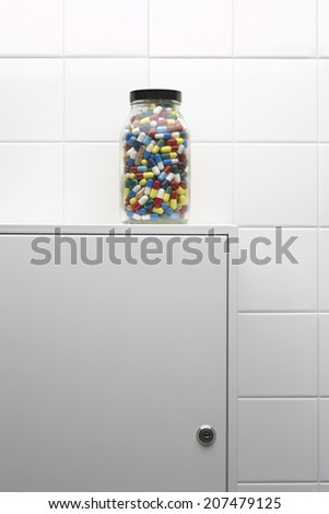 Jar of pills on bathroom cabinet - stock photo