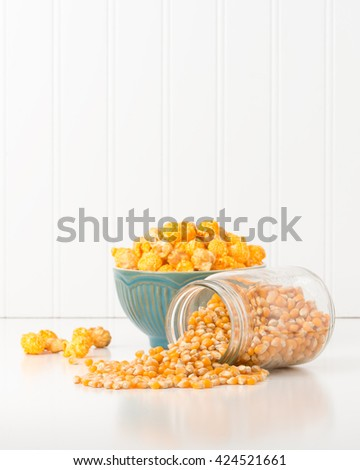 Jar of raw popcorn kernels with a bowl of popped corn in the background. - stock photo
