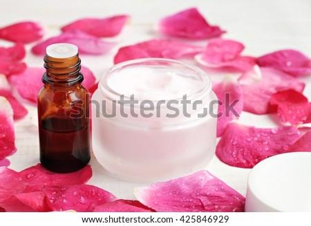 Jar of soft pinkish skin care cream, fragrance, bright pink fresh rose petals moistened. Gorgeous aroma body care spa. - stock photo