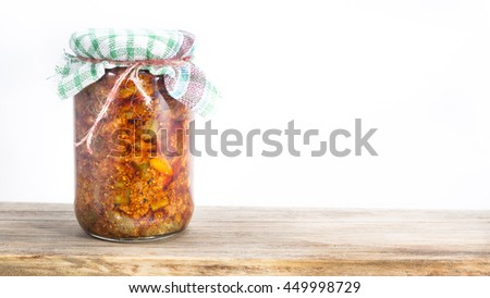 Jar of south indian homemade pickle on a wooden table - white background