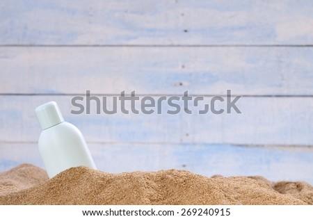 Jar of sunscreen on the beach sand. - stock photo