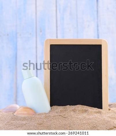 Jar of sunscreen on the beach sand and blackboard. - stock photo