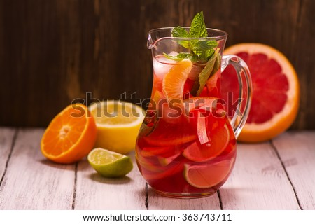 Jar of traditional red spanish sangria drink with different citrus fruits and mint over grunge wooden background. Selective focus - stock photo