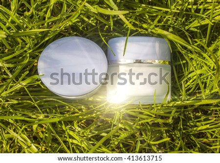 Jar with a cream on a background of green grass. Natural cosmetic. - stock photo