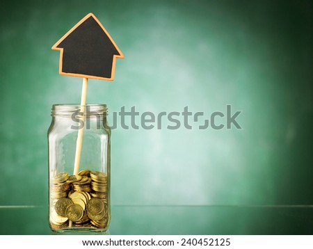 jar with black board house shaped  - stock photo