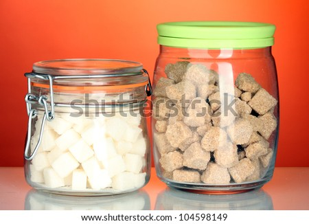 Jar with brown cane sugar lump and sugar-bowl with white lump sugar isolated on white - stock photo