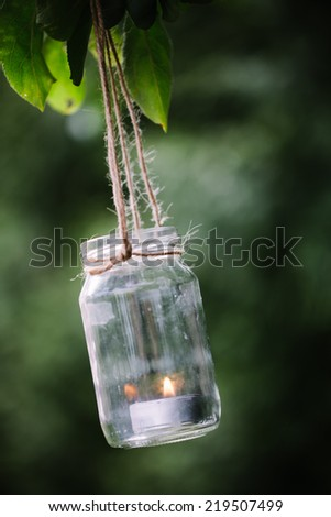 Jar with burning candle hanging on a tree. - stock photo