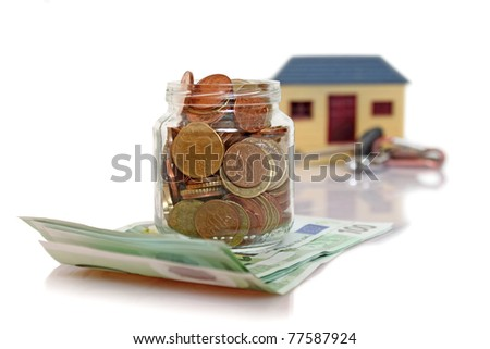 jar with coins in front of blurry house - stock photo