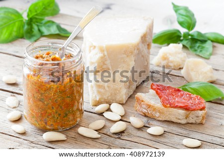 Jar with dried tomatoes pesto prepared with dried tomatoes in olive oil, basil, parmesan cheese and almonds. - stock photo