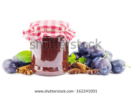Jar with plum butter, plums and spices on white - stock photo