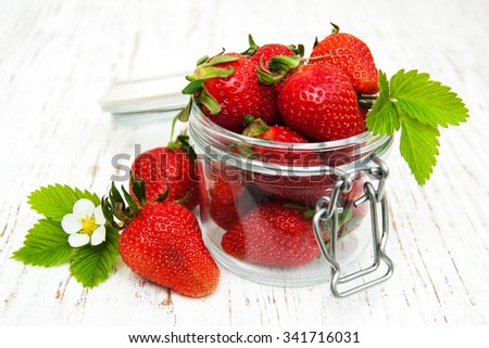 Jar with strawberries on a old wooden background