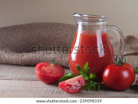 jar with tomato juice and tomatoes on a wooden table - stock photo