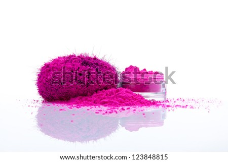 Jar with vivid makeup shadows and pile of pink powder with fuzy applicator - stock photo