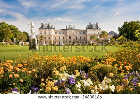 Jardin du Luxembourg with the Palace and statue. Few flowers are in front and blue sky behind. - stock photo