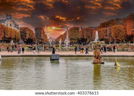Jardins du Luxembourg, Paris, France in autumn. Orange leafs and multicolored plants. Fountain and lake. Sunet with dramatic orange sky./Jardins du Luxembourg, Paris, France - stock photo